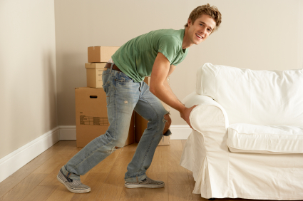 Young Man Moving Sofa Into New Home
